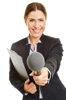 Lächelnde Frau mit Klemmbrett hält Mikrofon in die Kamera